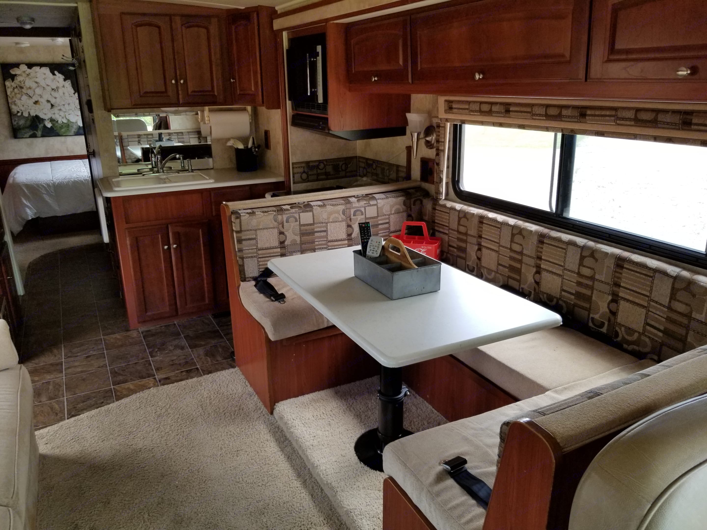 Dining table with wrap around seating and the kitchen beyond that.. Winnebago Vista 2011