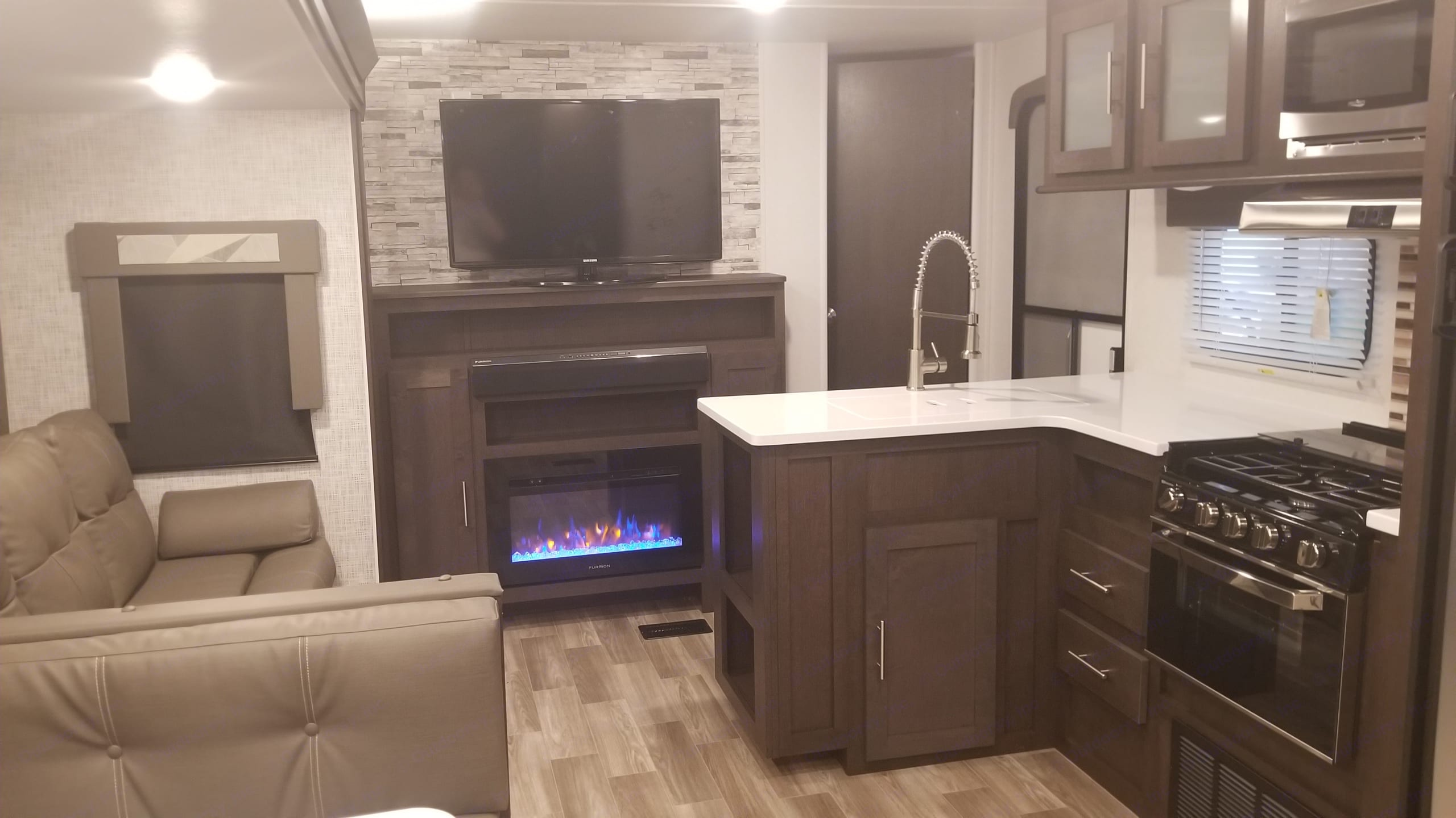 Fireplace with or without heating, great for winter or just for ambiance. Large flatscreen TV with swivel mount, DVD player, full fireplace mantle with storage. . Forest River Wildwood 2020
