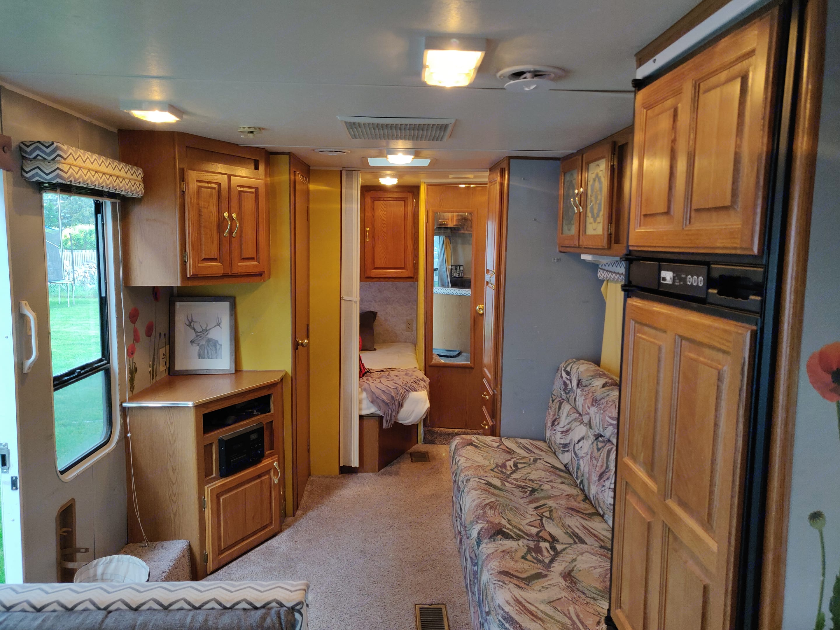 Left Side of Camper when entering. Fold out couch bed, Full Size Bed and Single bunk in back with Bathroom sink, mirror, toilet, and shower.. Jayco Eagle M 242 FK 1998