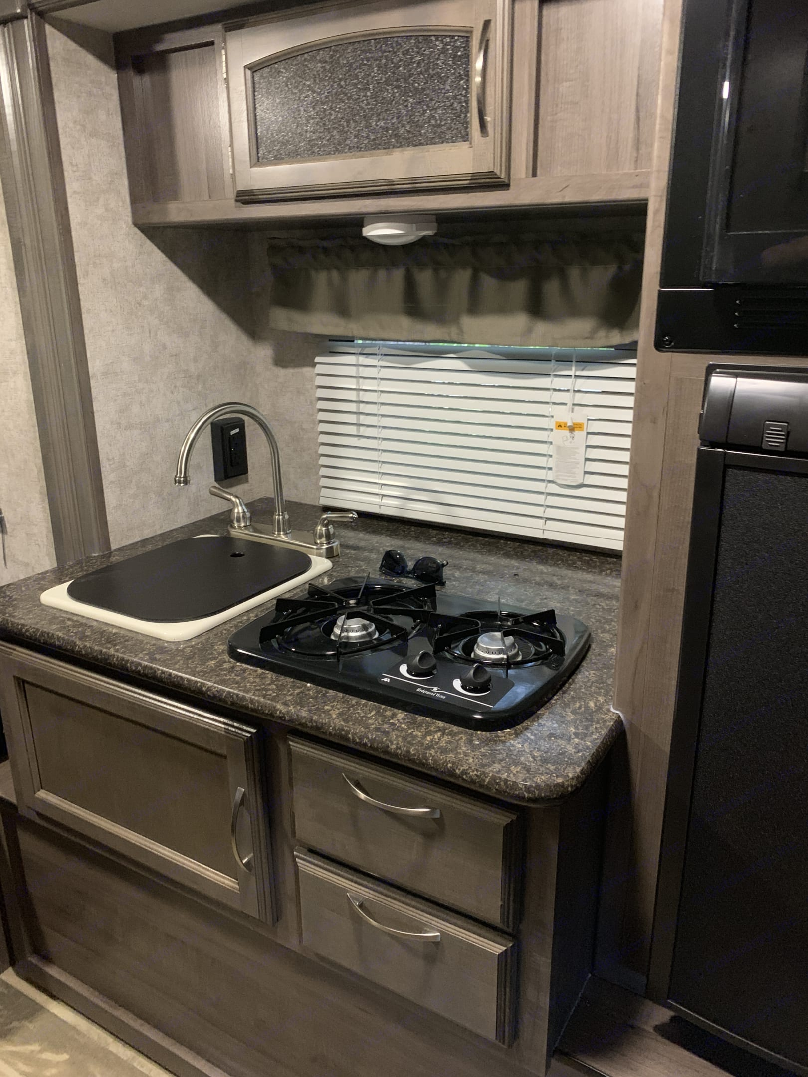 Kitchen including sink, microwave/convection oven, and fridge.. Winnebago Winnie Drop 2018