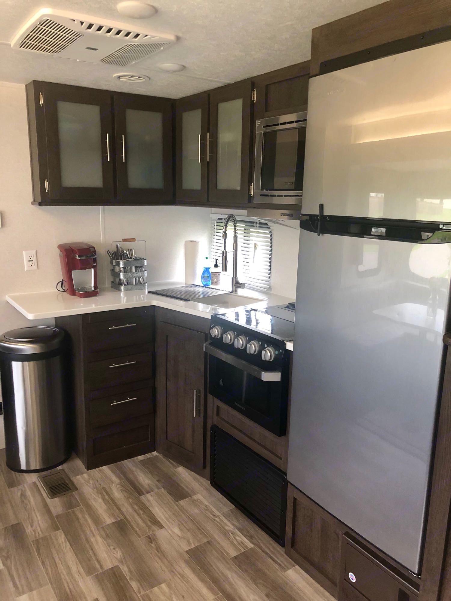 Kitchen (microwave, stove, oven, spacious fridge & freezer, single-cup Keurig coffee maker). Forest River Salem 2020