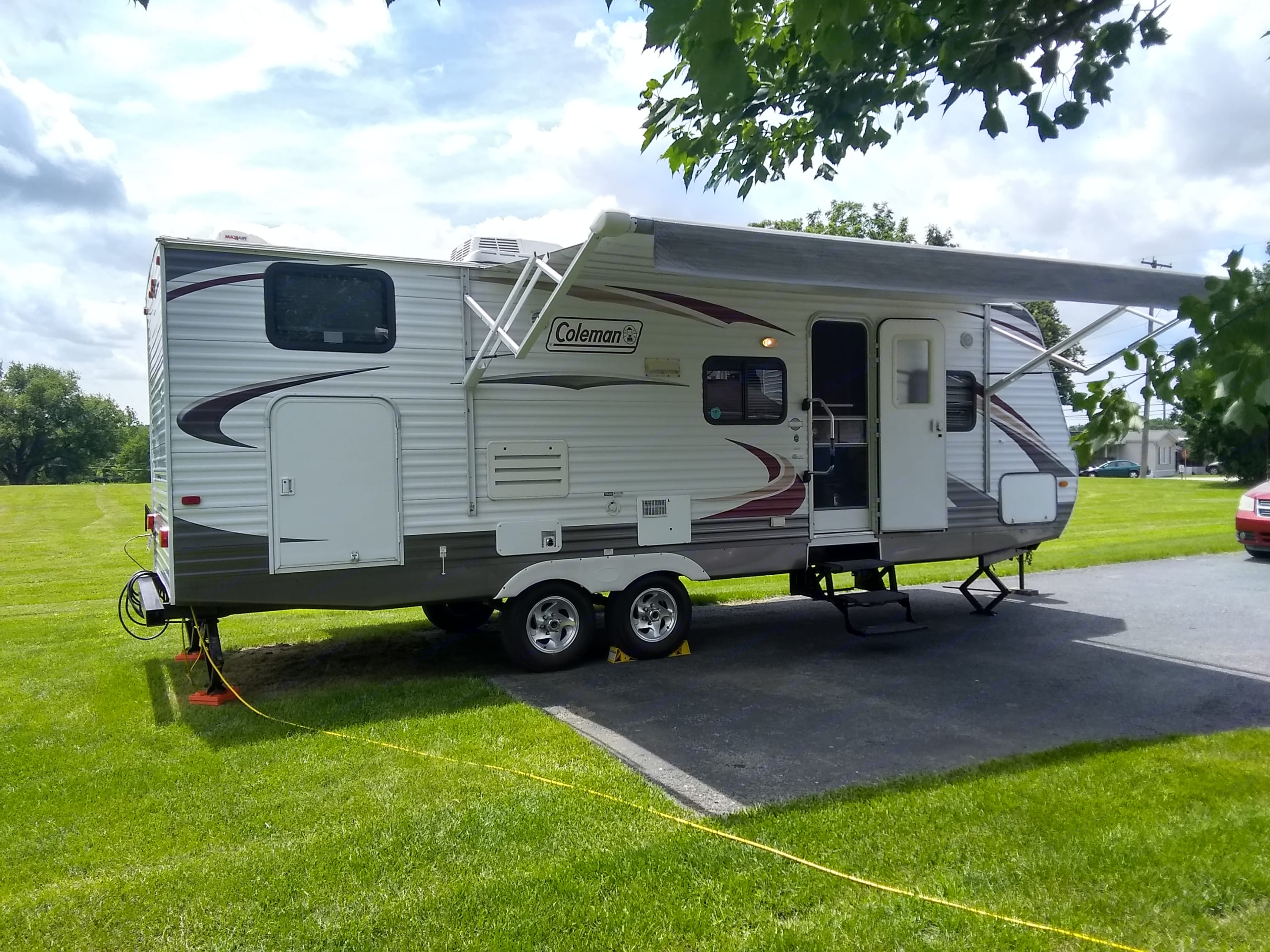 Exterior Entry side with a porch light, Exterior power outlet, 3 step entry with gold away grab assist handle, and a large power retractable awning to provide shade from the sun and protection from the rain.. Dutchmen Coleman 2010