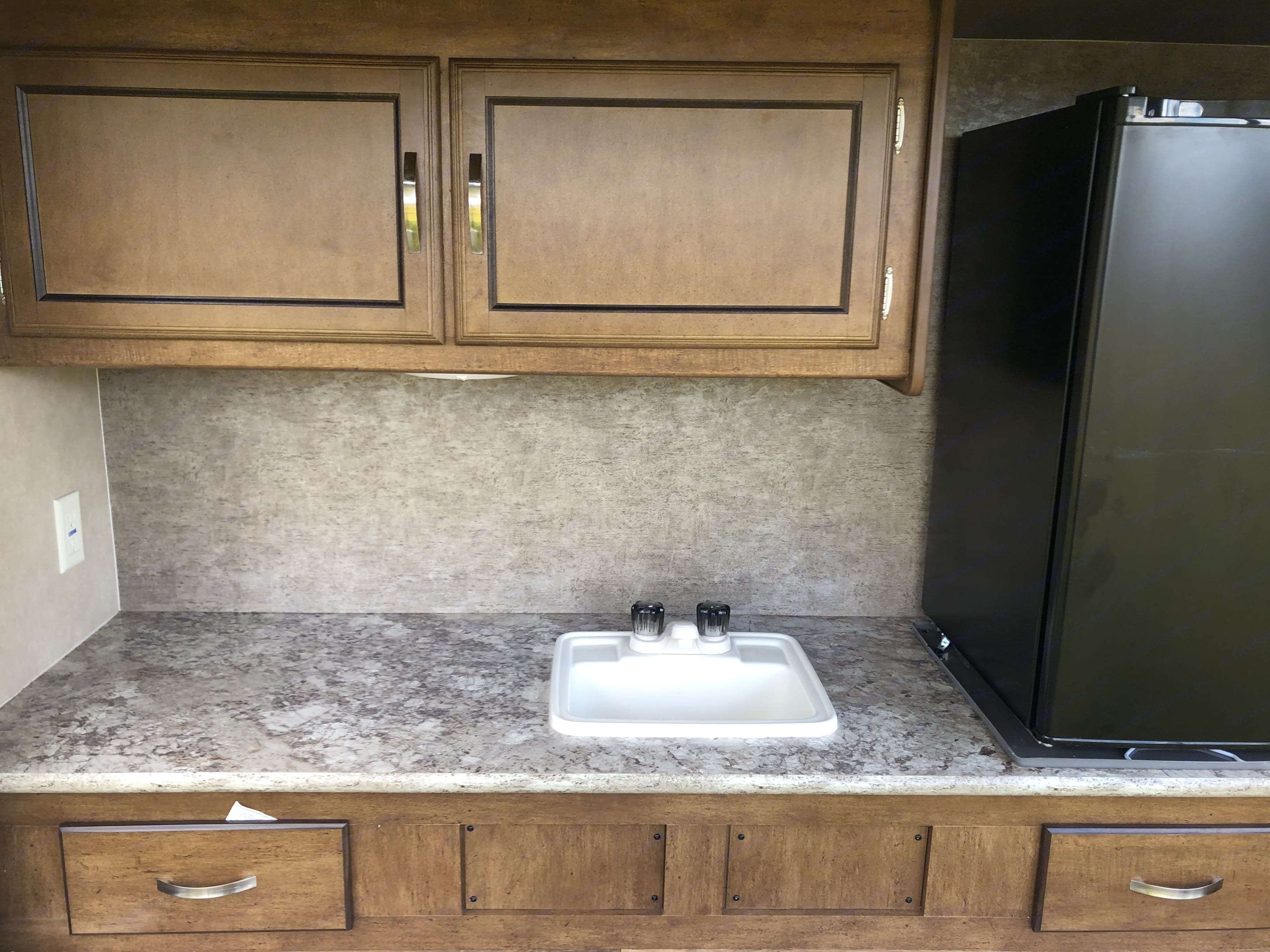 Outdoor kitchen complete with storage, sink, stove/ grill and mini fridge for lots of fun outdoors! . Forest River Wildwood X-Lite 2017