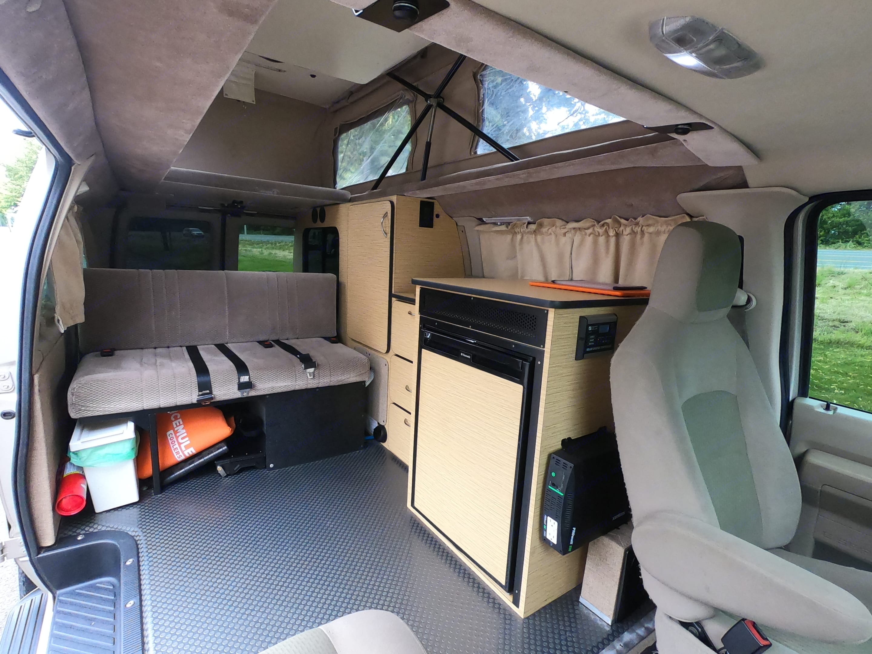 3 seat belts on bench seat that folds out to a bed, Pop top has a bed. Kitchen has sink and fridge. Comes with portable cook stove.. Ford Econoline 2009