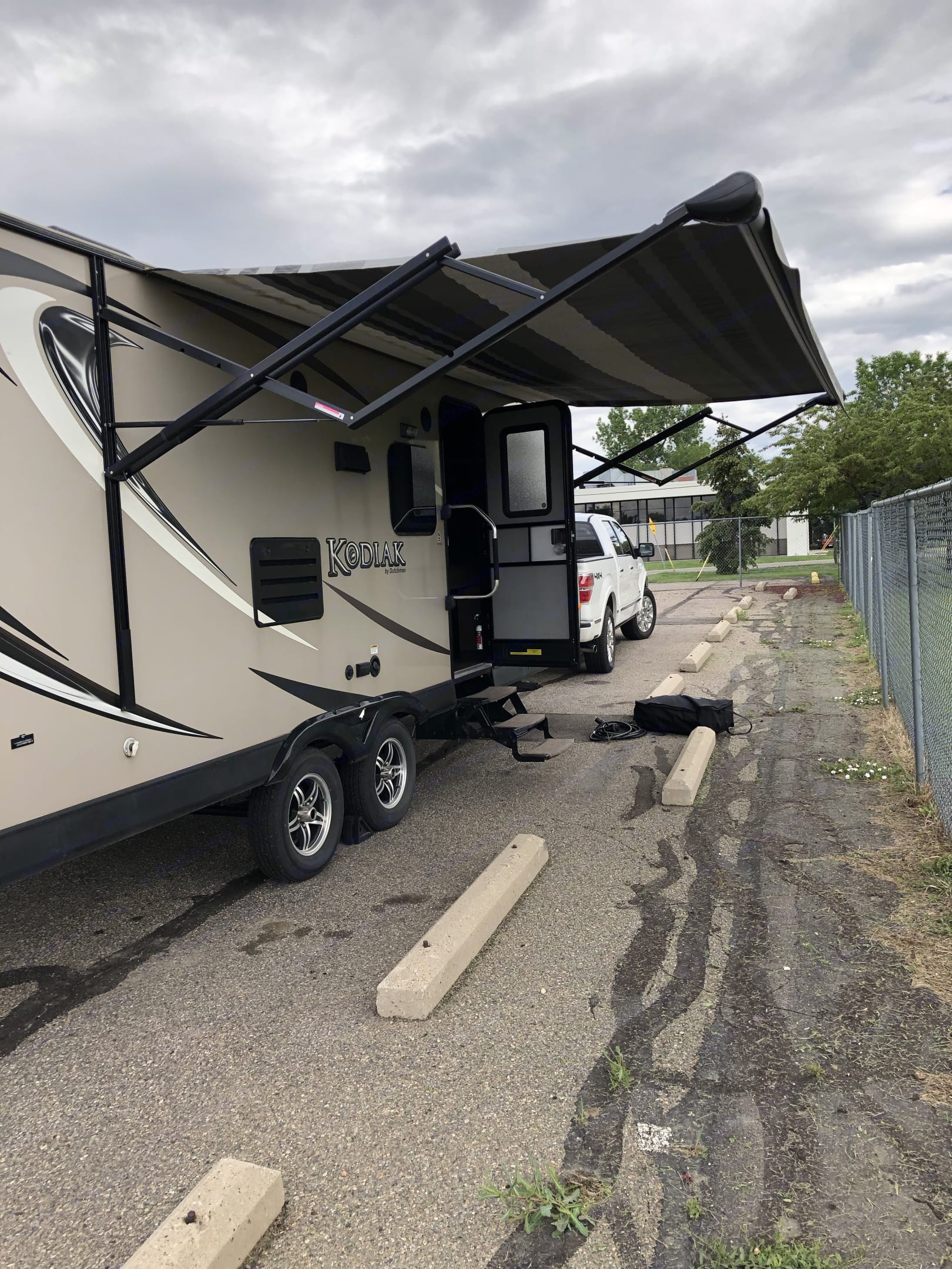 door with 3 step fold down stairs and 15' electric awning.  Exterior speaker. exterior electrical outlet. . Dutchmen Kodiak 2014