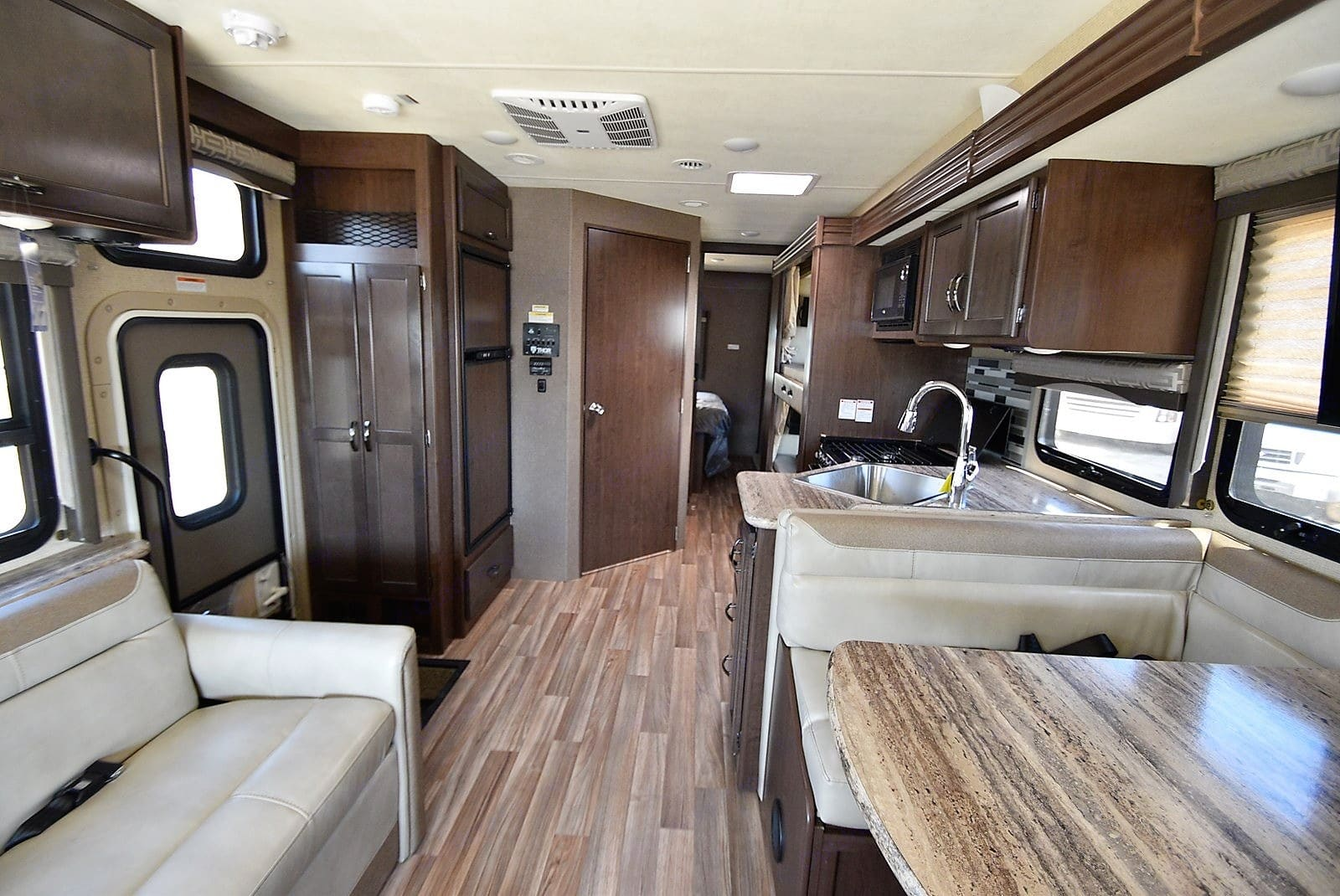 Rearward view of the interior.  Full 7 feet of interior height.  Refrigerator/freezer on the left, Control Center panel on wall, bathroom door, and bunks on the right.  Master bedroom further back down the hallway.  Onboard generator is controlled via the Control Center panel.  2 rooftop air conditioners, 1 in ceiling near kitchen, 1 in ceiling in master bedroom (50-amp service required to use both at same time, otherwise 30-amp service is fine).. Thor Motor Coach A.C.E 30.2 2019
