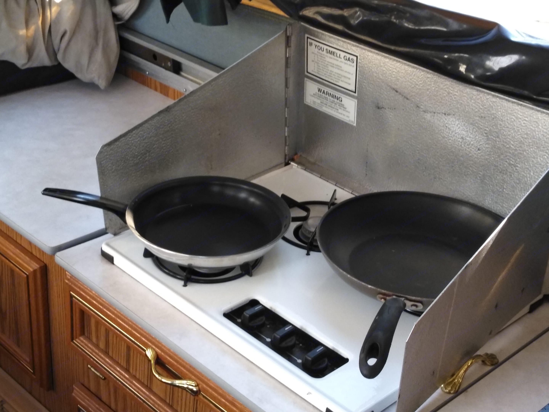 Two pans on the three-burner stove.. Jayco Jay Series 1996