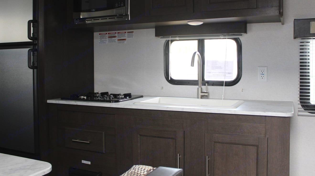 Kitchen: refrigerator, freezer, stove top, microwave, sink. Forest River Wildwood 2020