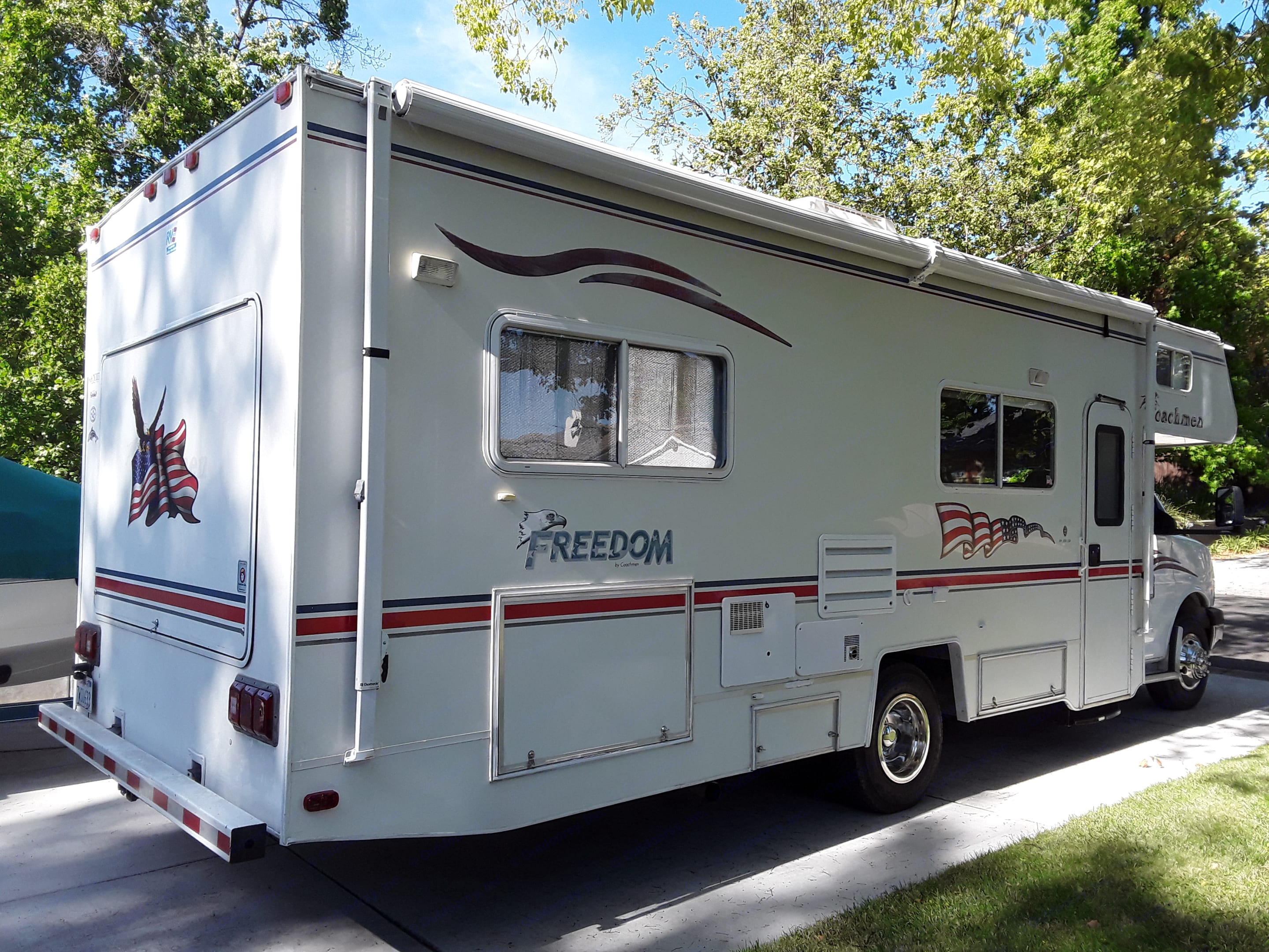 18 foot awning/shade.  Storage compartments on sides plus the back door opens up to reveal shelves and pegboard.  Many small items are stored here for your use.. Coachmen Freedom Express 2004