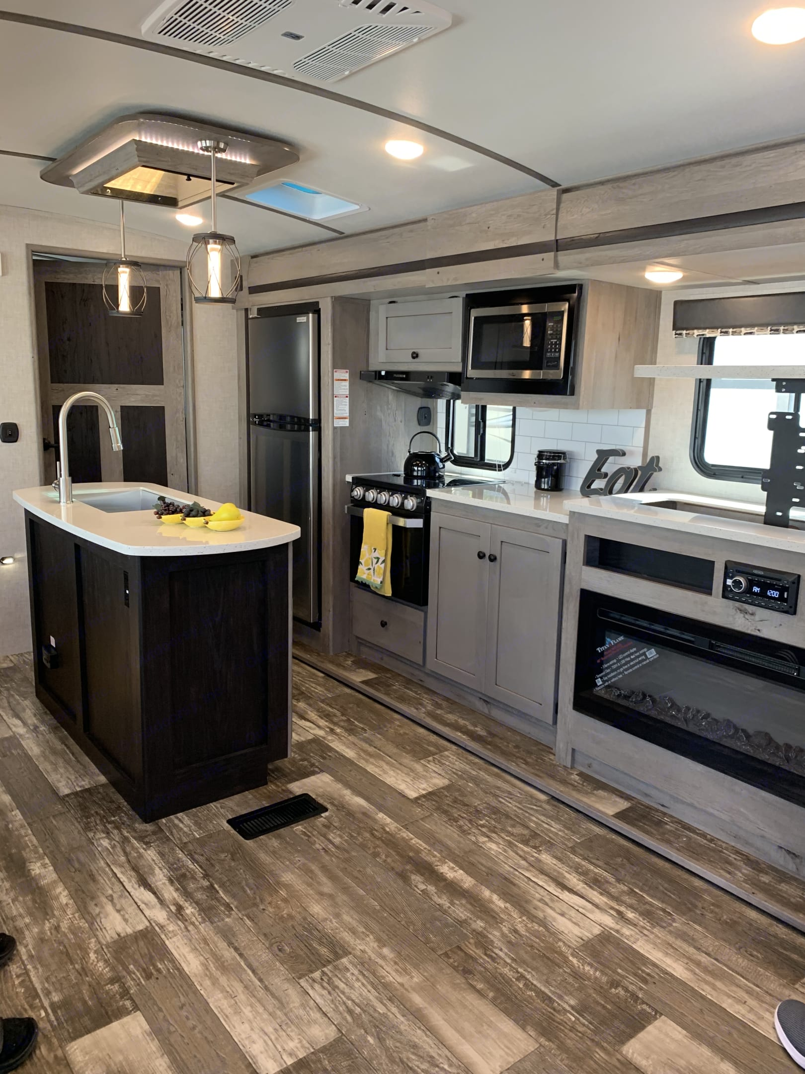 Kitchen, with island, fireplace, TV comes up from behind the fireplace. TV is installed (not shown in the pic). Stove with 3 burners (gas), microwave, both Fridge that runs on batteries when driving to keep things cool.. Keystone Outback Terrain 2020