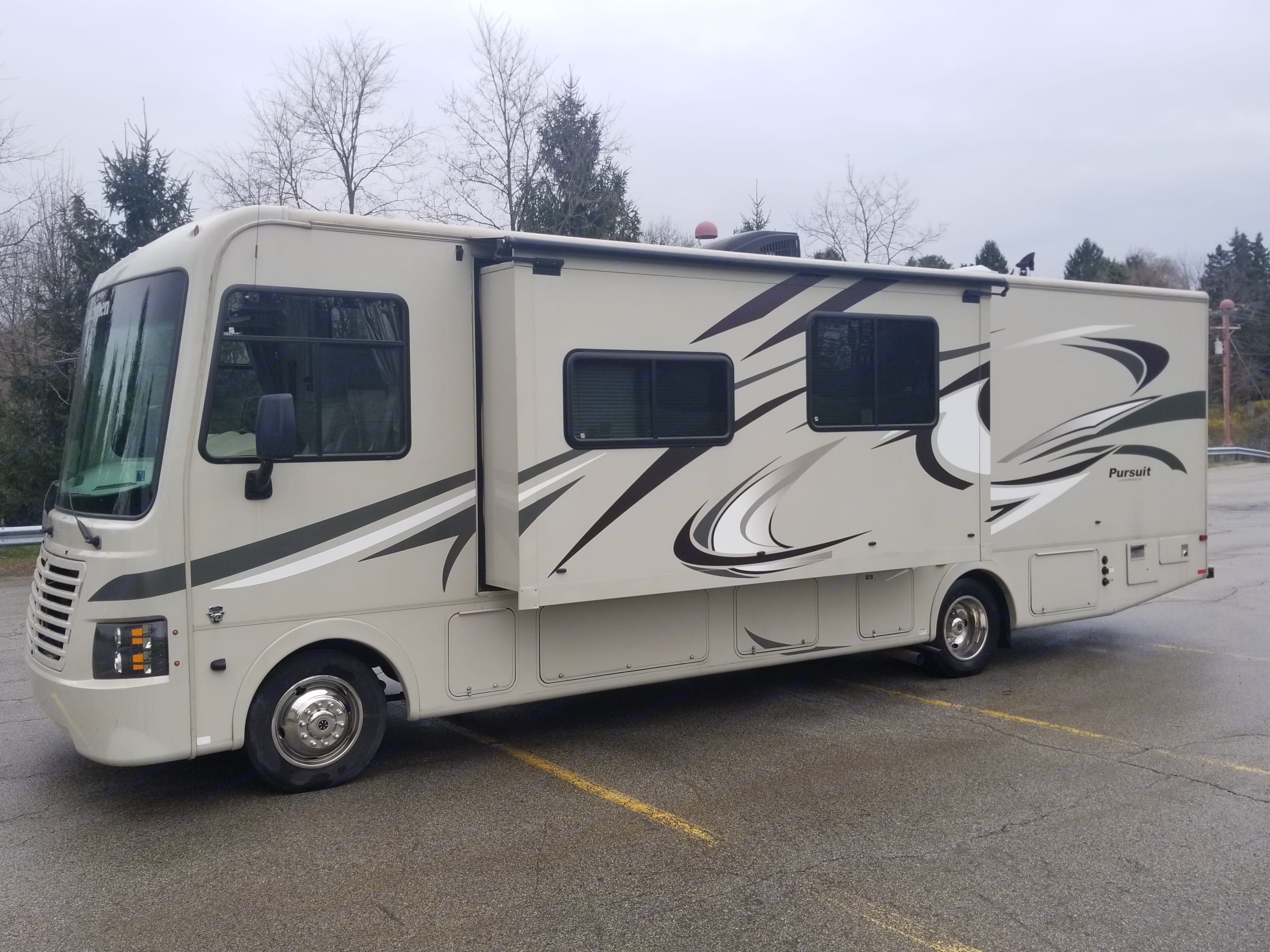 Driver's side exterior view with slide out extended. Coachmen Pursuit 2014
