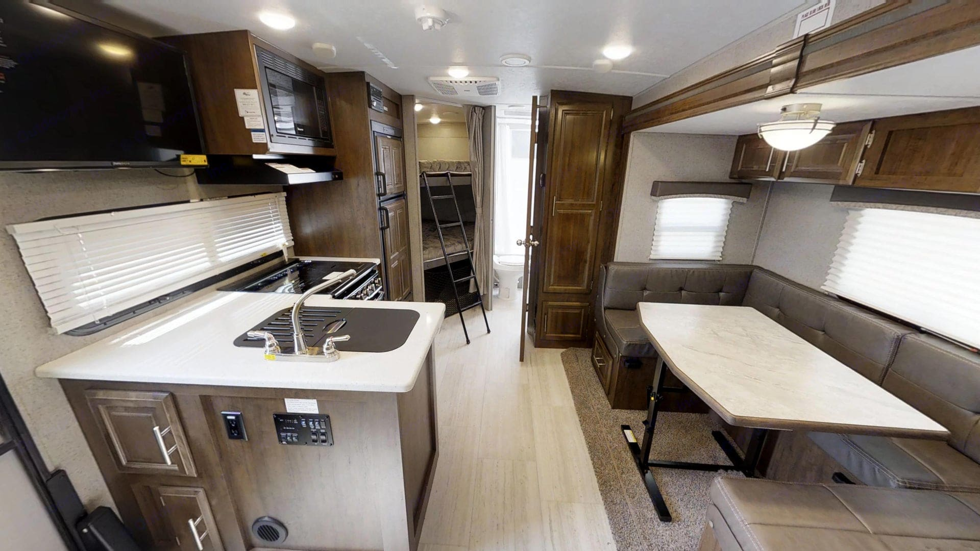 View into spacious kitchen and slide out dinette with double sized bunks and bathroom in the background.. Forest River Rockwood Mini Lite 2019
