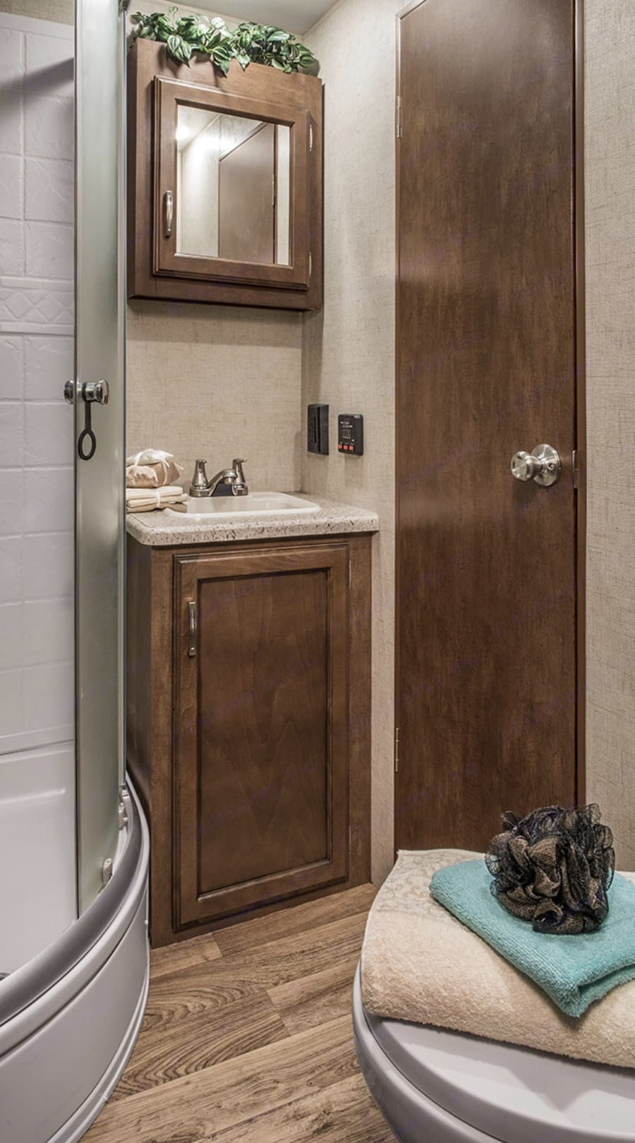 Shower and bathroom off of master bedroom with queen bed at front of trailer . Venture Rv Sporttrek 2017