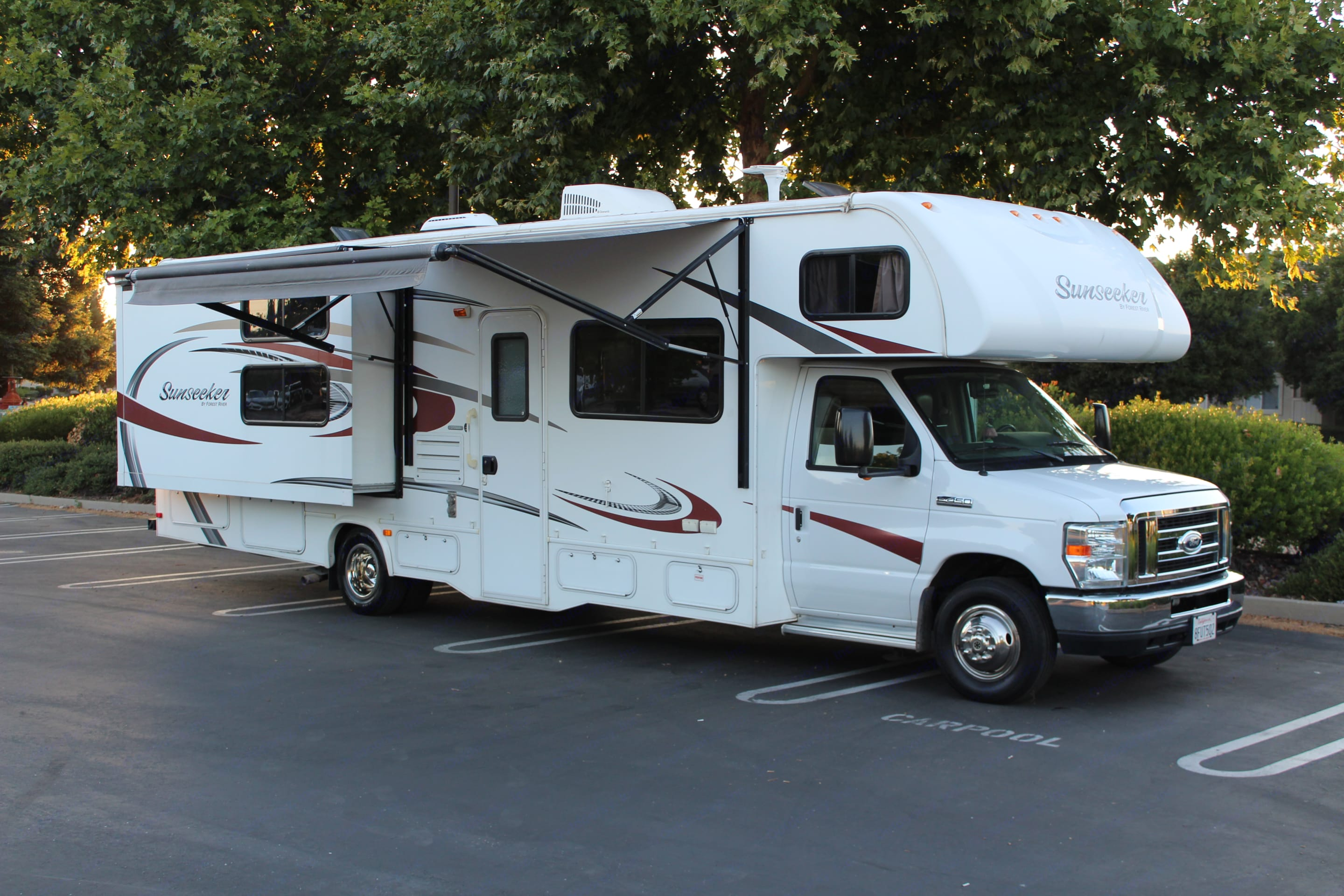 RV with awning out and slide out to allow room for bunk area and master bedroom.. Forest River Sunseeker 2015