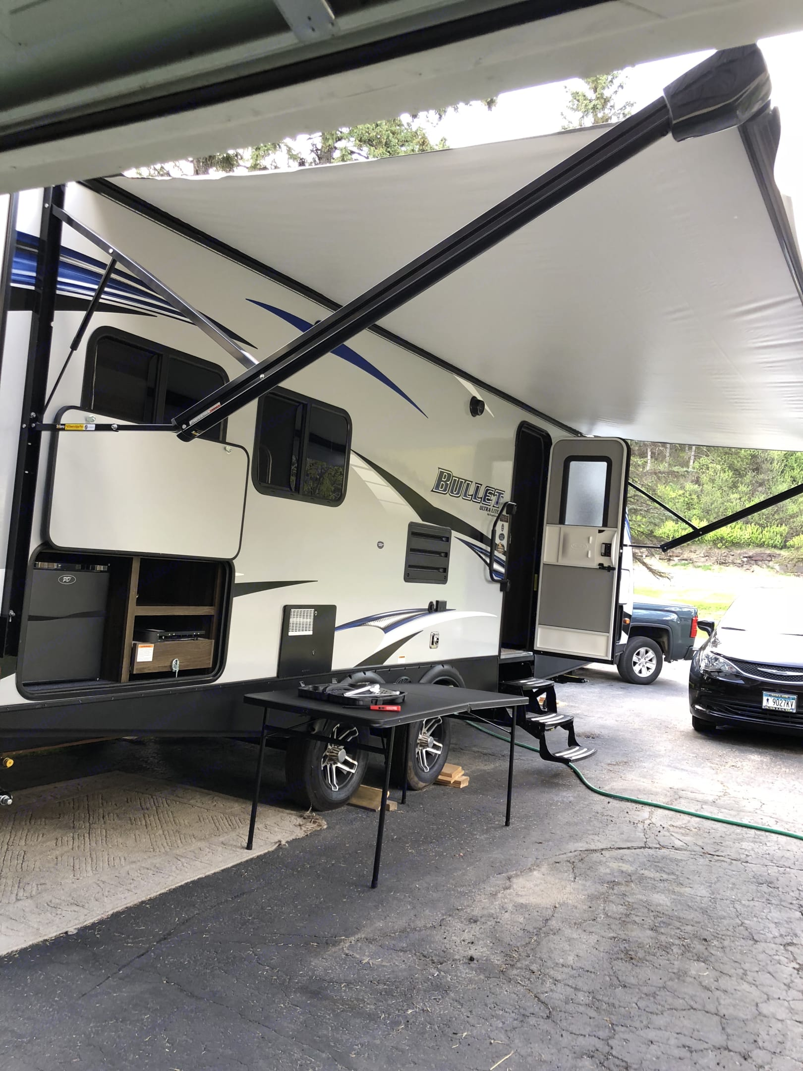 Picture is side of travel trailer showing entrance and outdoor kitchen. Keystone Bullet 2018