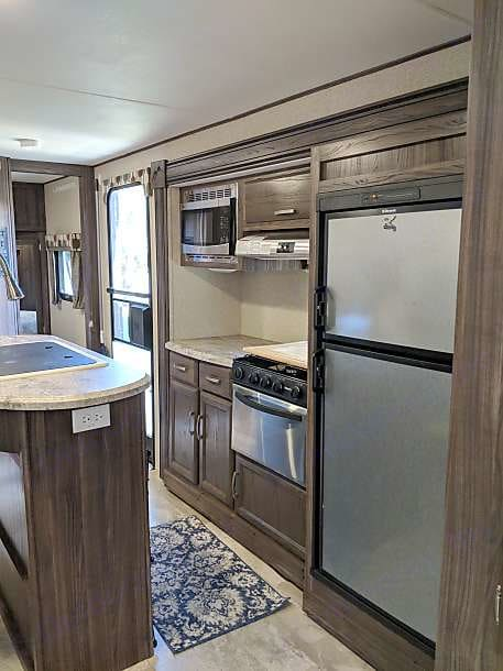 Kitchen with sink, fridge/freezer, stove/oven, and plenty of space. Kitchen also comes fully stocked with dishes, pots and pans, silverware, cleaning supplies, and dish towels. . Coachmen Apex 2017