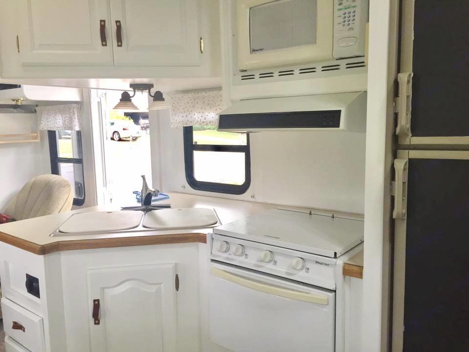 Bright and Spacious kitchen with Microwave, refrigerator, 3 - burner stove, and propane oven. Forest River Sunseeker 2003