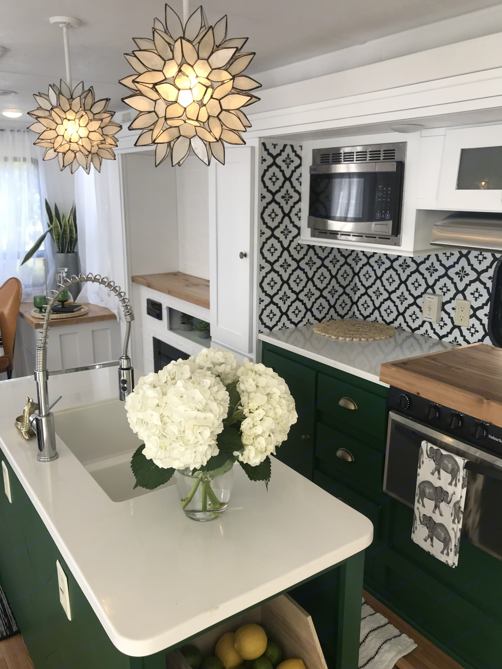 Mid century, mix metal kitchen that is highly contemporary. Large island and customized cutting board stove top cover perfect for coming a gourmet meal with friends.. Forest River Wildwood 2018