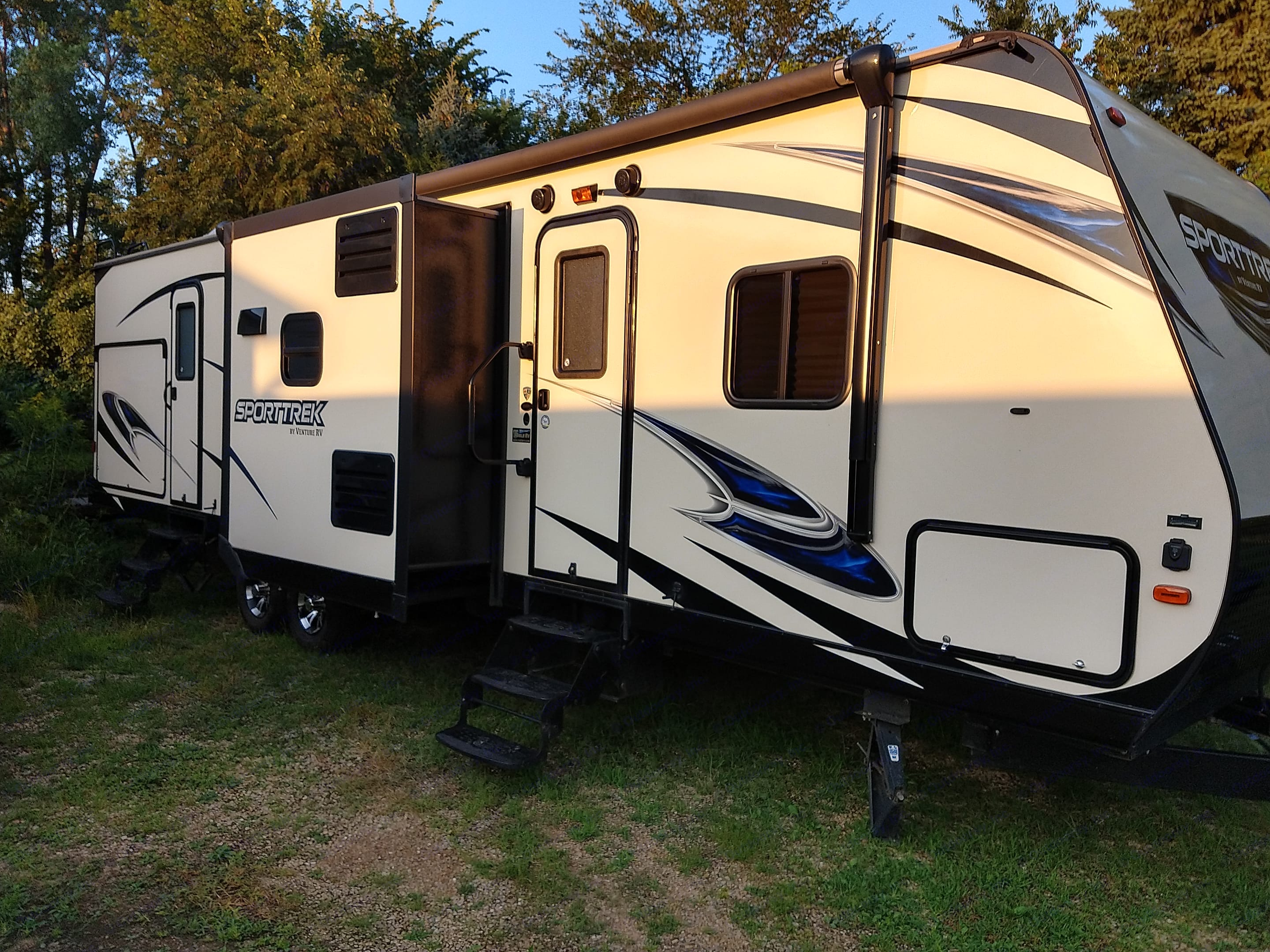 Right side of Camper with the kitchen slide out. The out door kitchen door is visible in the rear along with the rear door for the outside bathroom entrance. Front door is the main. Entrance. Power awning with LED lights.. Venture Rv Sporttrek 2017