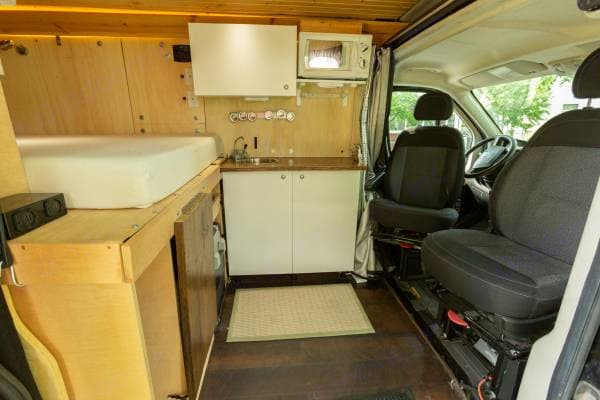The wooden table unhooks and props up on a wooden leg, and the fridge pulls out to sit on, making a nice workspace and dinner table.. Dodge Promaster 1500 2014