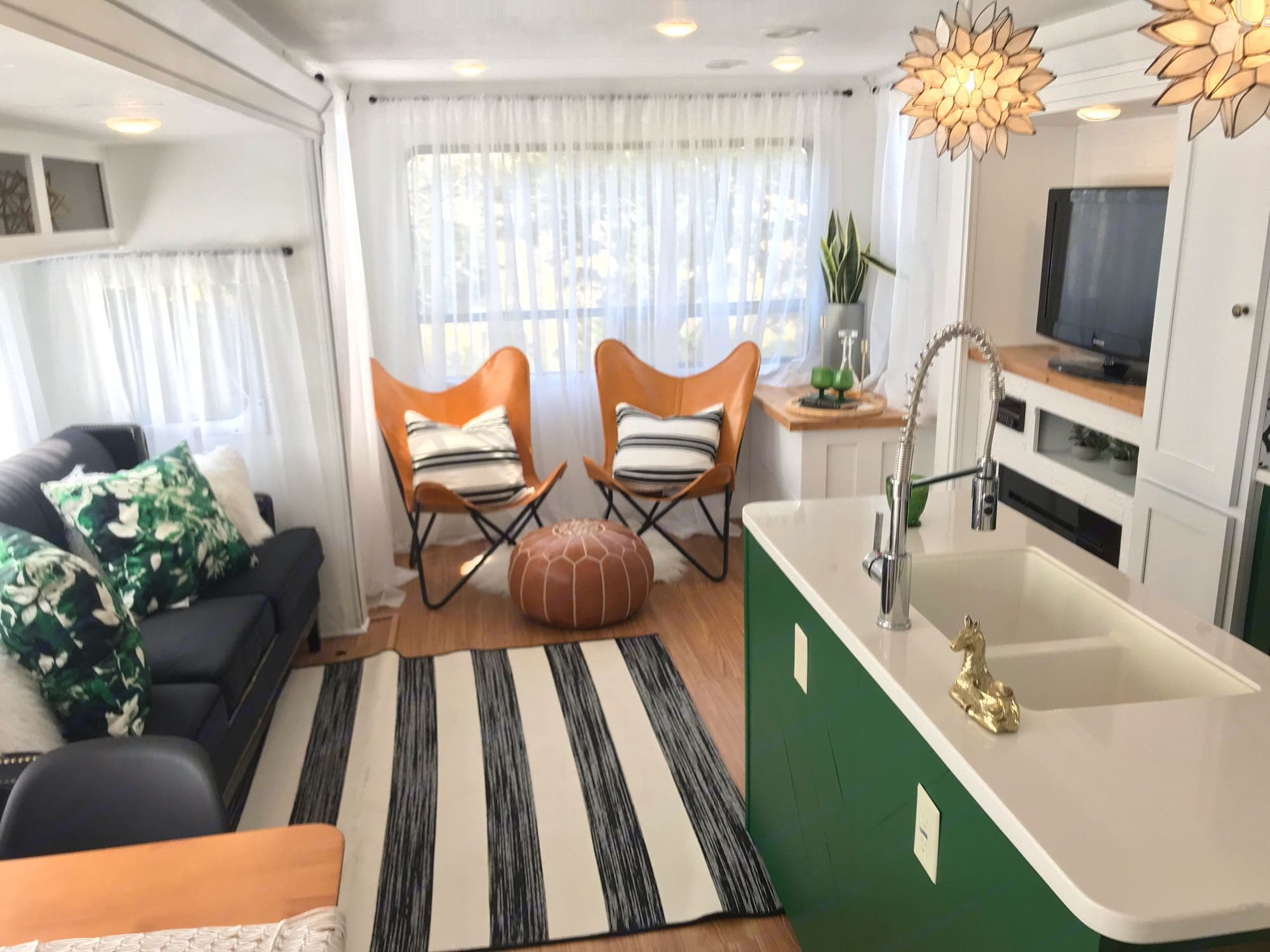 Living area with Mid Century Modern butterfly chairs that are perfect for a cozy book overlooking that big back window perfect for overlooking the lake or Hill Country.. Forest River Wildwood 2018
