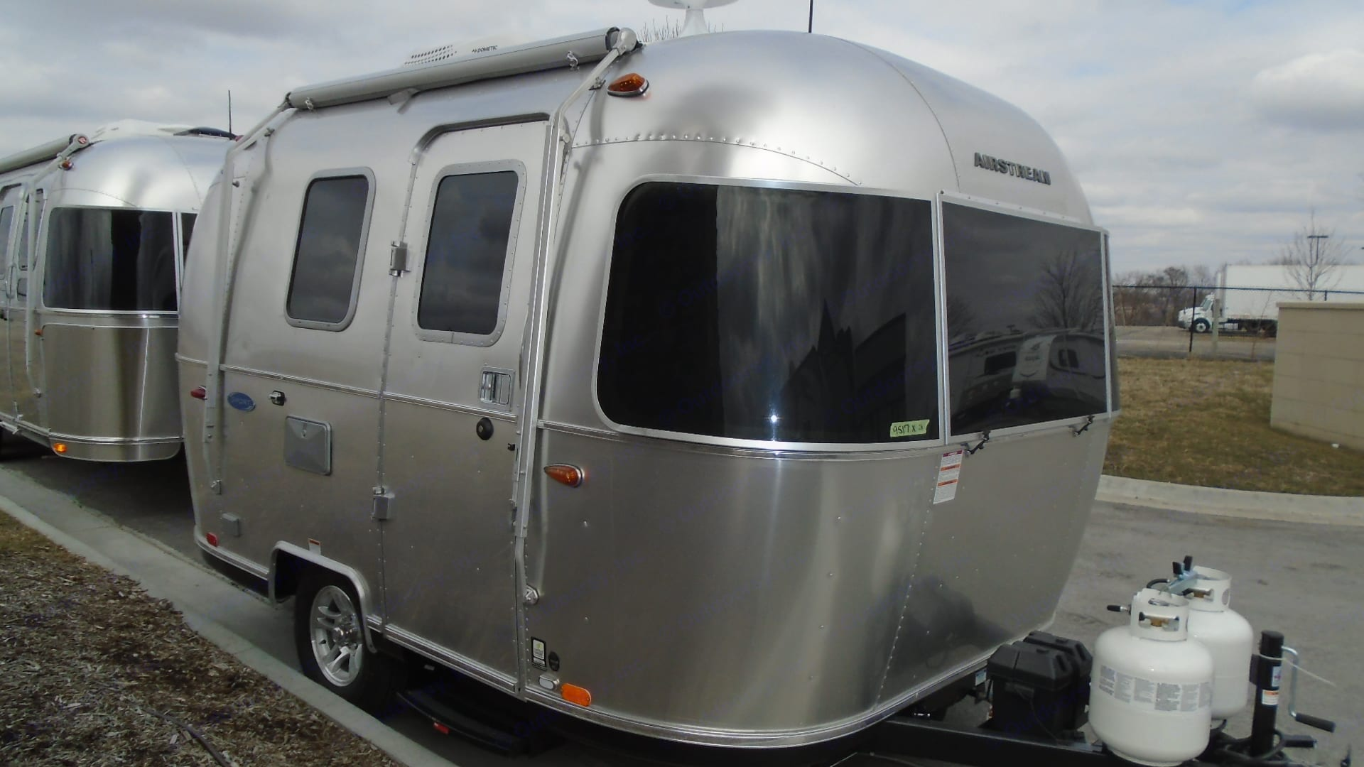 Tinted front windows open for a panoramic view at the dining table.. Airstream Sport 2019