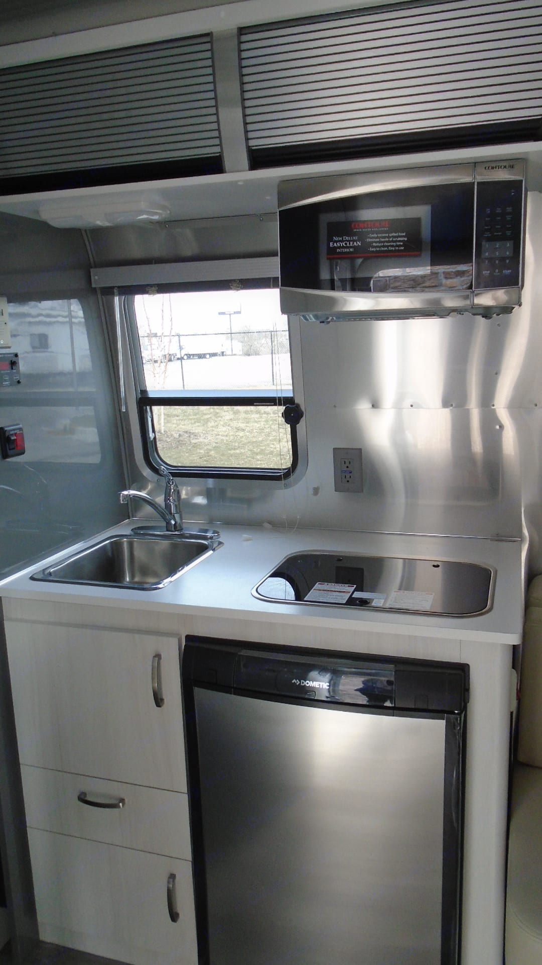 2-burned gas range with tempered glass cover next to the kitchen sink.. Airstream Sport 2019