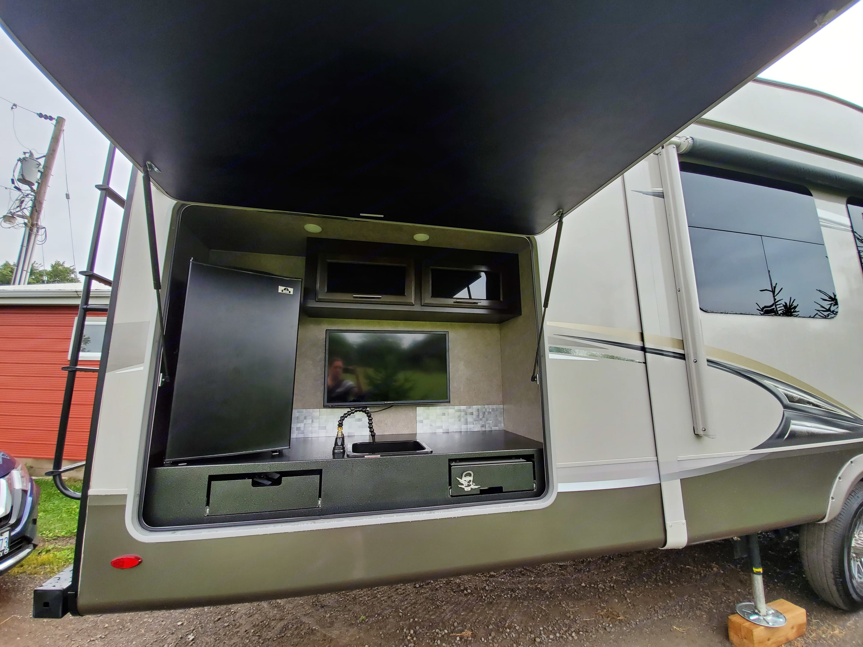 Outdoor kitchen equipped with: bar fridge, storage, sink, TV and grill. Jayco Eagle 347BHOK 2018
