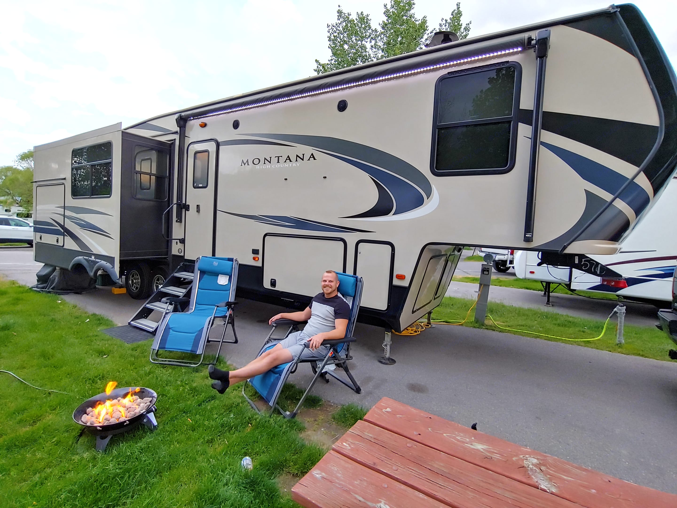 Exterior LED lighting, speakers, large awning, mood-lit mini-kitchen with fridge, microwave, and stove, and reclining camp chairs.. Keystone Montana High Country 2019
