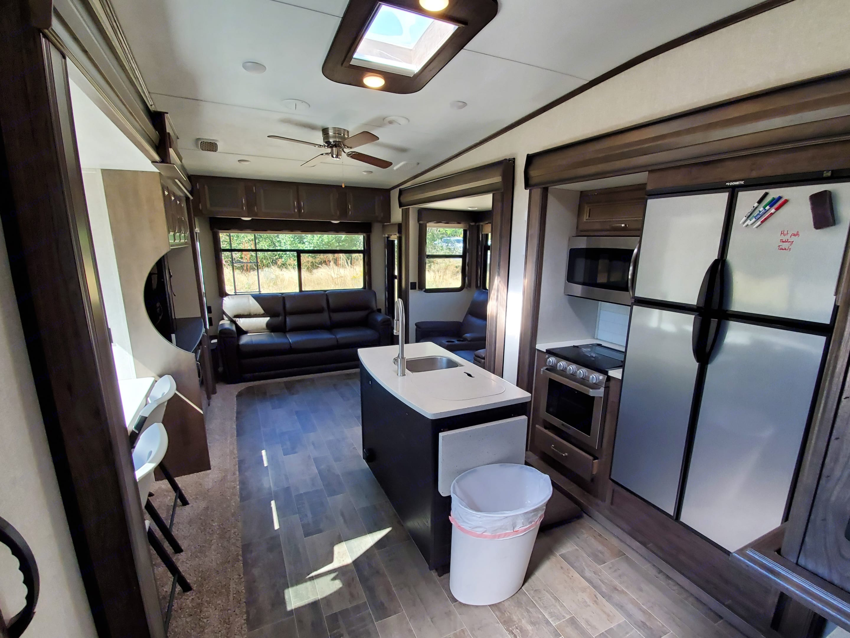 Spacious kitchen / living area featuring: island sink (dual basin), gas stove and oven, fridge/freezer, microwave, sky light, and ceiling fan.. Keystone Montana High Country 2019
