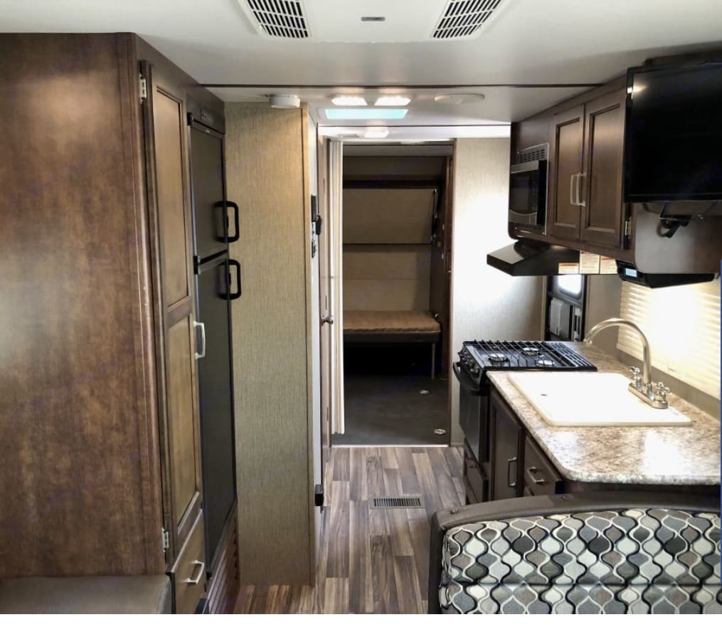 Kitchen area with microwave, stove, oven, and sink. TV in dining area facing main bed as well.. Keystone Outback 2017