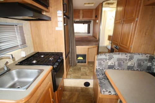kitchen sink, 3 stove, microwave on the top, oven beneath, 2-door fridge, big standing cabinets and several storage drawers. Coachmen Freelander 2008