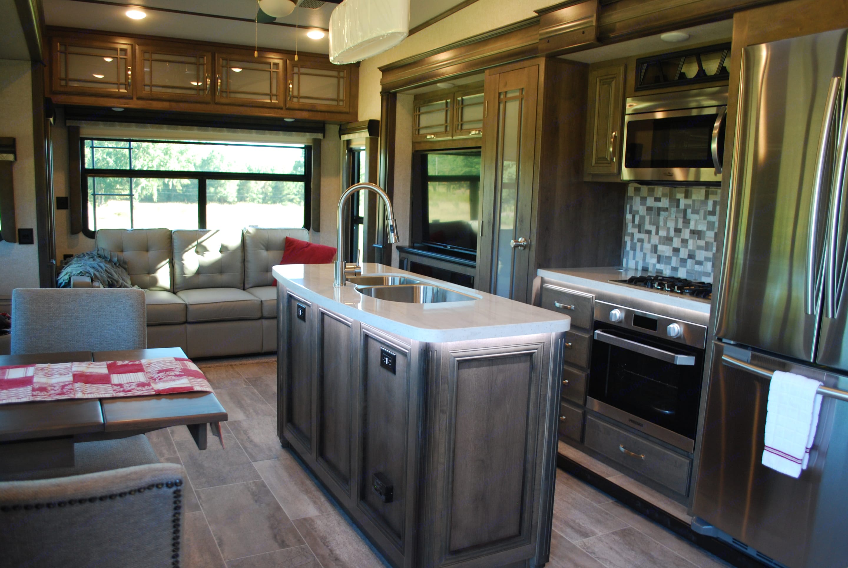 Wow! You just can't feel cramped in this spacious area. There's plenty of seating and plenty of storage space. And, yes, that's a full-size refrigerator/freezer!. Keystone Montana Legacy 3931FB 2019