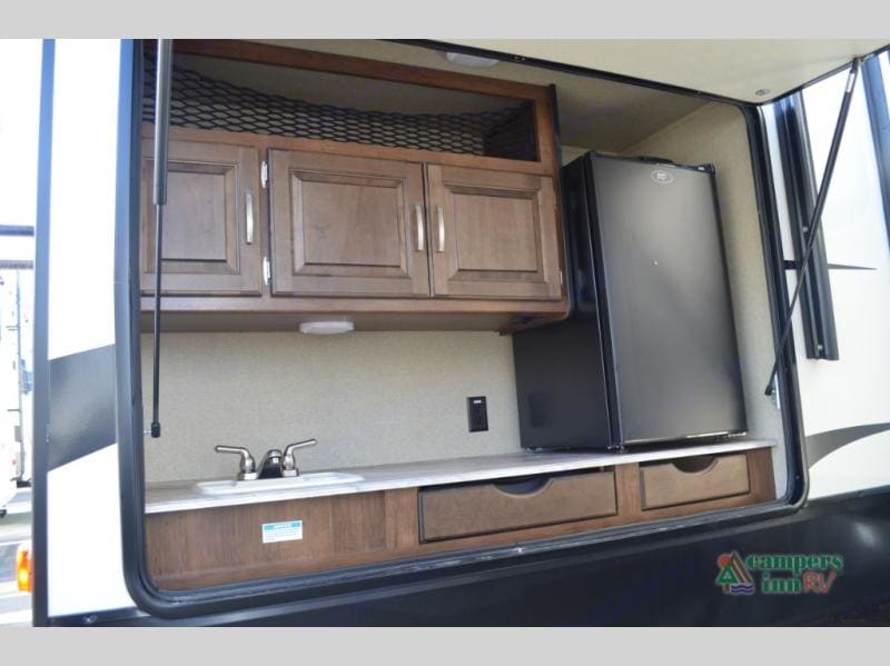 The outdoor kitchen includes a 2 burner gas stove, a sink with hot and cold water, a refrigerator and plenty of cabinet / drawer space.  . Grand Design Reflection 2019