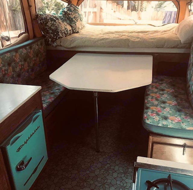 More table next to cute vintage functioning fridge. . Starcraft Camping Trailers 1970