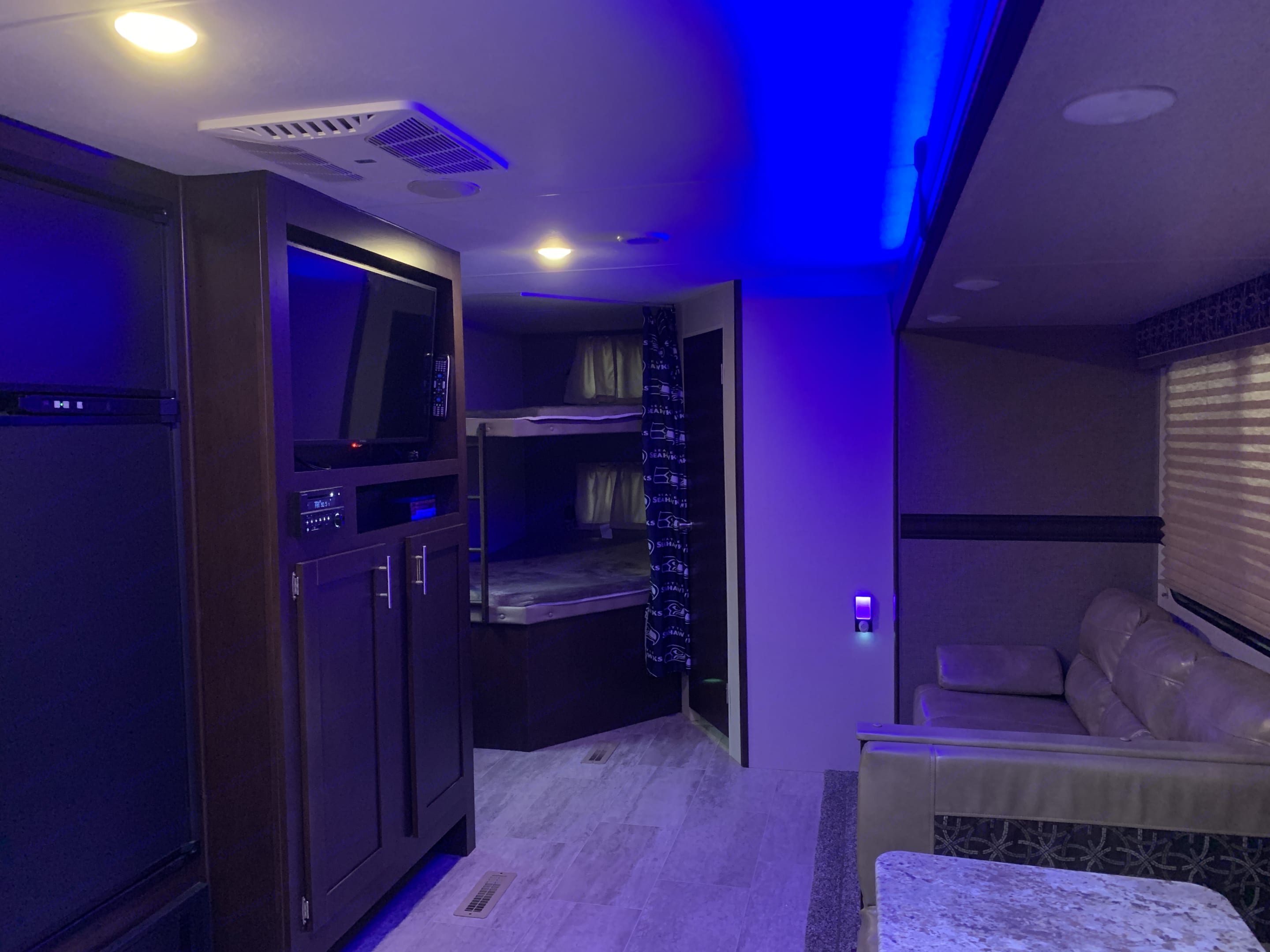 Entertainment center with DVD player, Bluetooth, radio. Indoor and outdoor speakers. Blue accent lighting, two bunks in the back. K-Z Manufacturing Sportsmen 2019