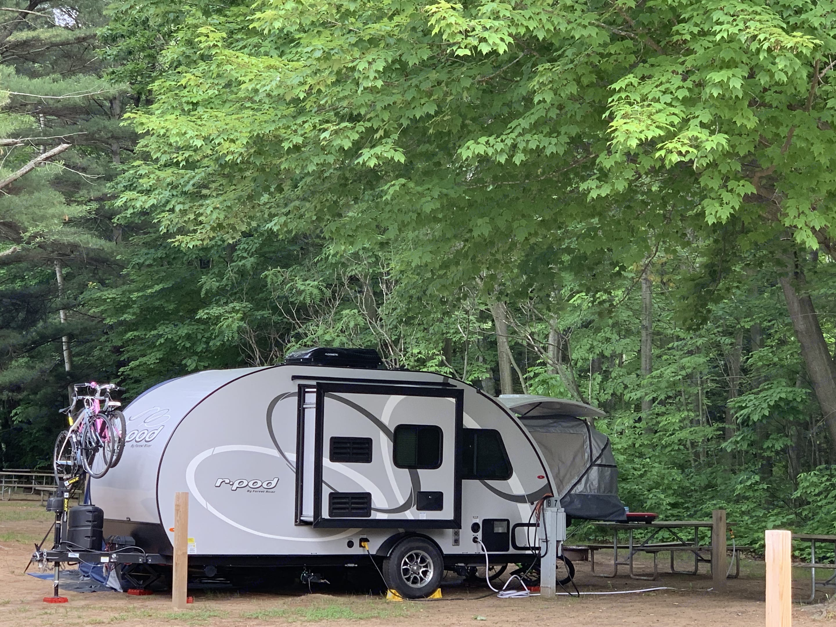 This is a side view of the camper with the JackIt front bike rack in use.  The slide is for the kitchen area.  There is even an Outdoor Shower!. Forest River R-Pod 2020