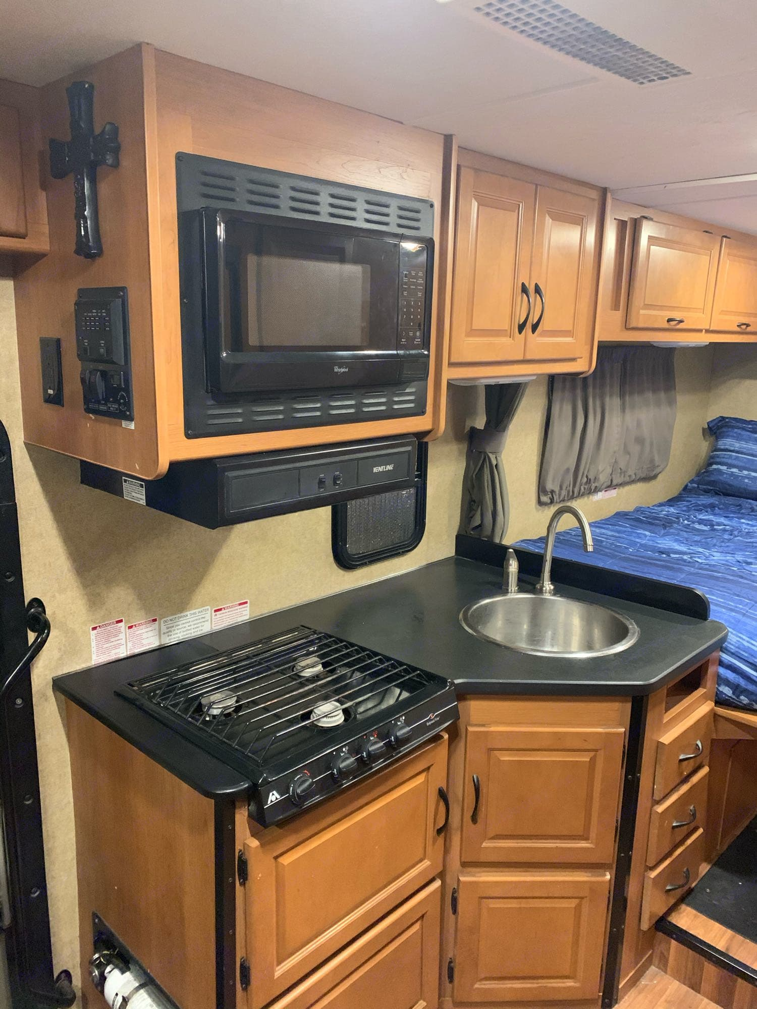 Kitchen area including microwave, gas stove and sink.. Thor Motor Coach Four Winds Majestic 2015