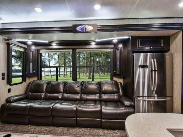 Luxurious living room Big windows and reclining massaging soft leather chairs with flip-down drink holders and USB chargers  and full-size refrigerator. Thor Motor Coach Road Warrior 427-RW 2018