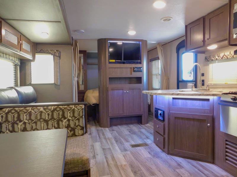 Area where couch is can be changed into a double bed as well another bed can be folded out where the kitchen table is.  Entertainment unit as well with lots of storage above.. Keystone Hideout 2015