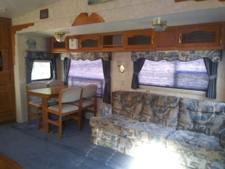 Living room slide out with dinette table, 4 chairs, and couch folds out into a bed.. Keystone Montana 2000