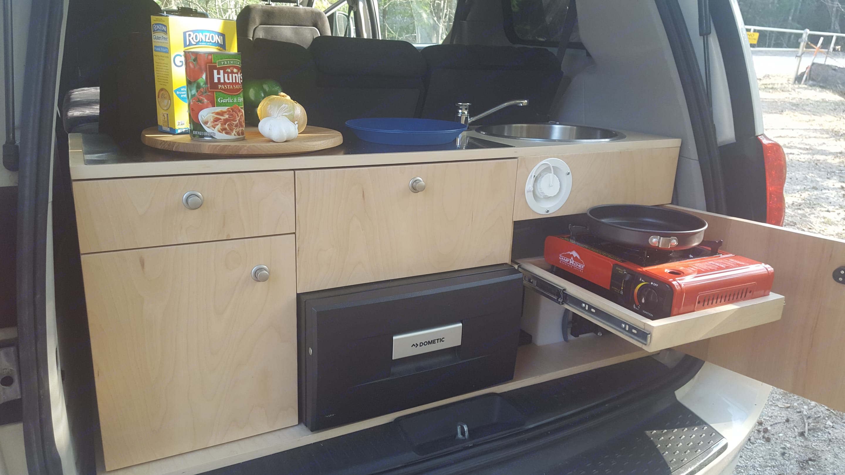 Your galley kitchen, fully equipped with utensils and cooking equipment for two.  Single burner propane/butane stove, 10 gallon hand pump fresh water system with 5 gallon grey water tank.  Dometic 12 volt drawer style refrigerator with a 31 quart capacity has plenty of space for your essentials!. Dodge Caravan 2012