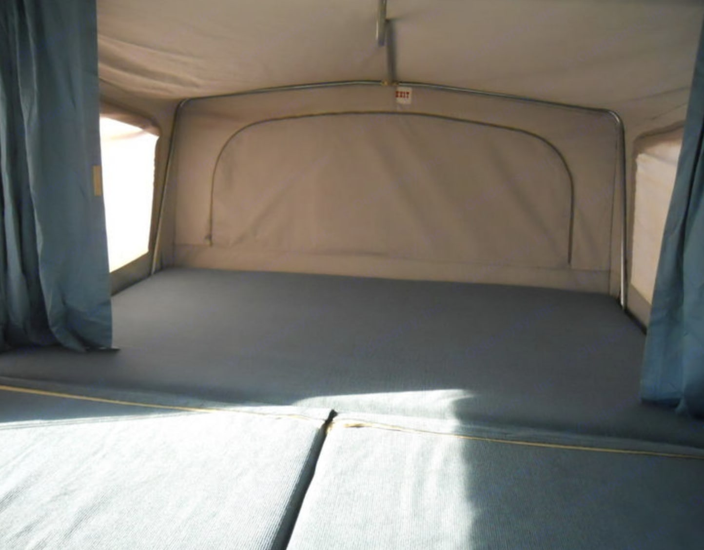King-sized bed and privacy curtains; also a ceiling hanging rod for clothes on this side. Jayco Designer 1995