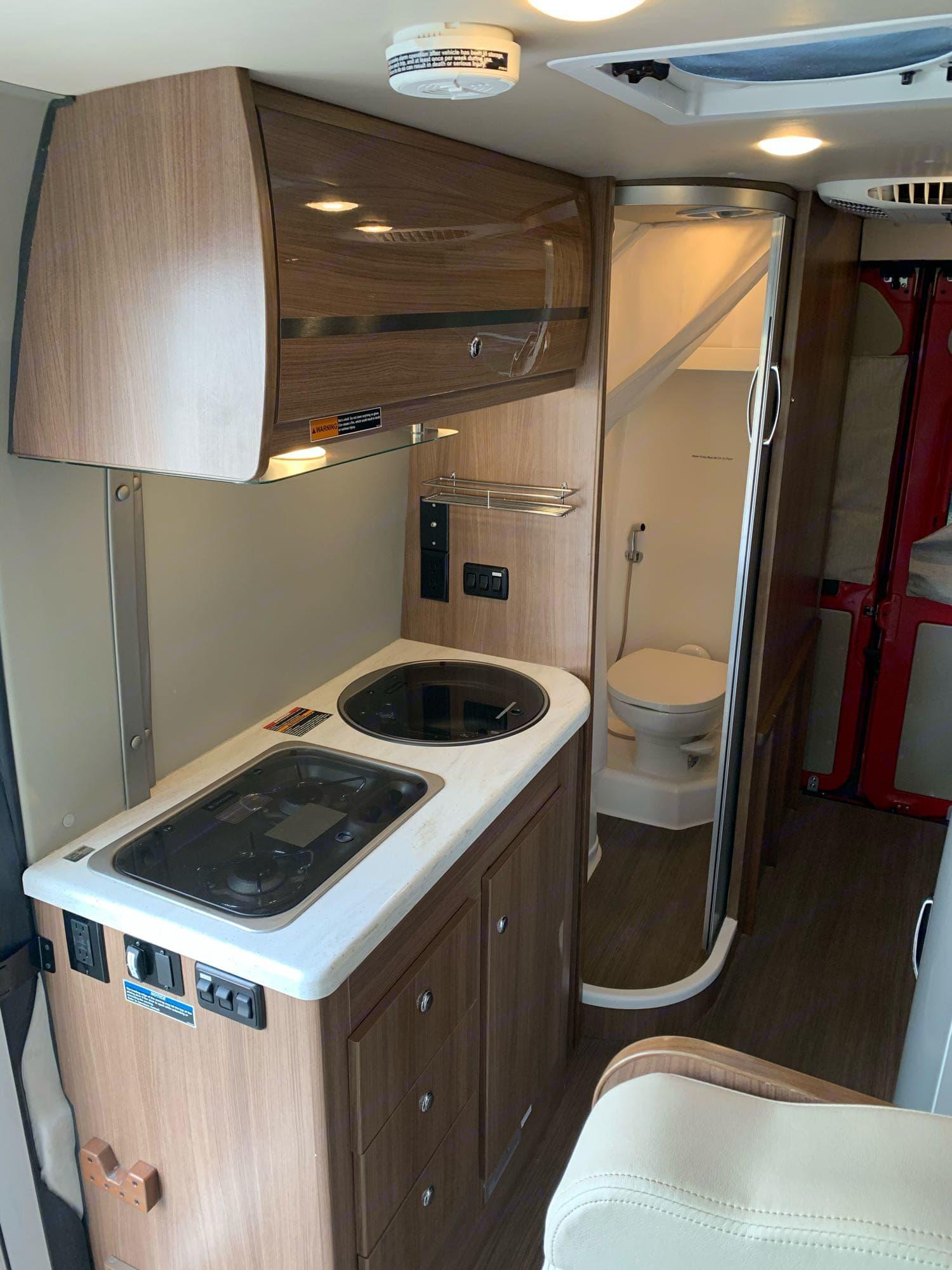 Kitchen stove and sink with over head storage.. Winnebago Travato 2016