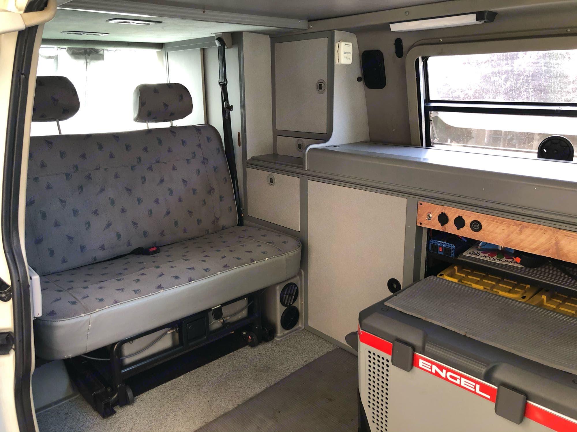 Bench seat slides forward then folds flat to a lower bed.. Volkswagen Eurovan Camper 1997