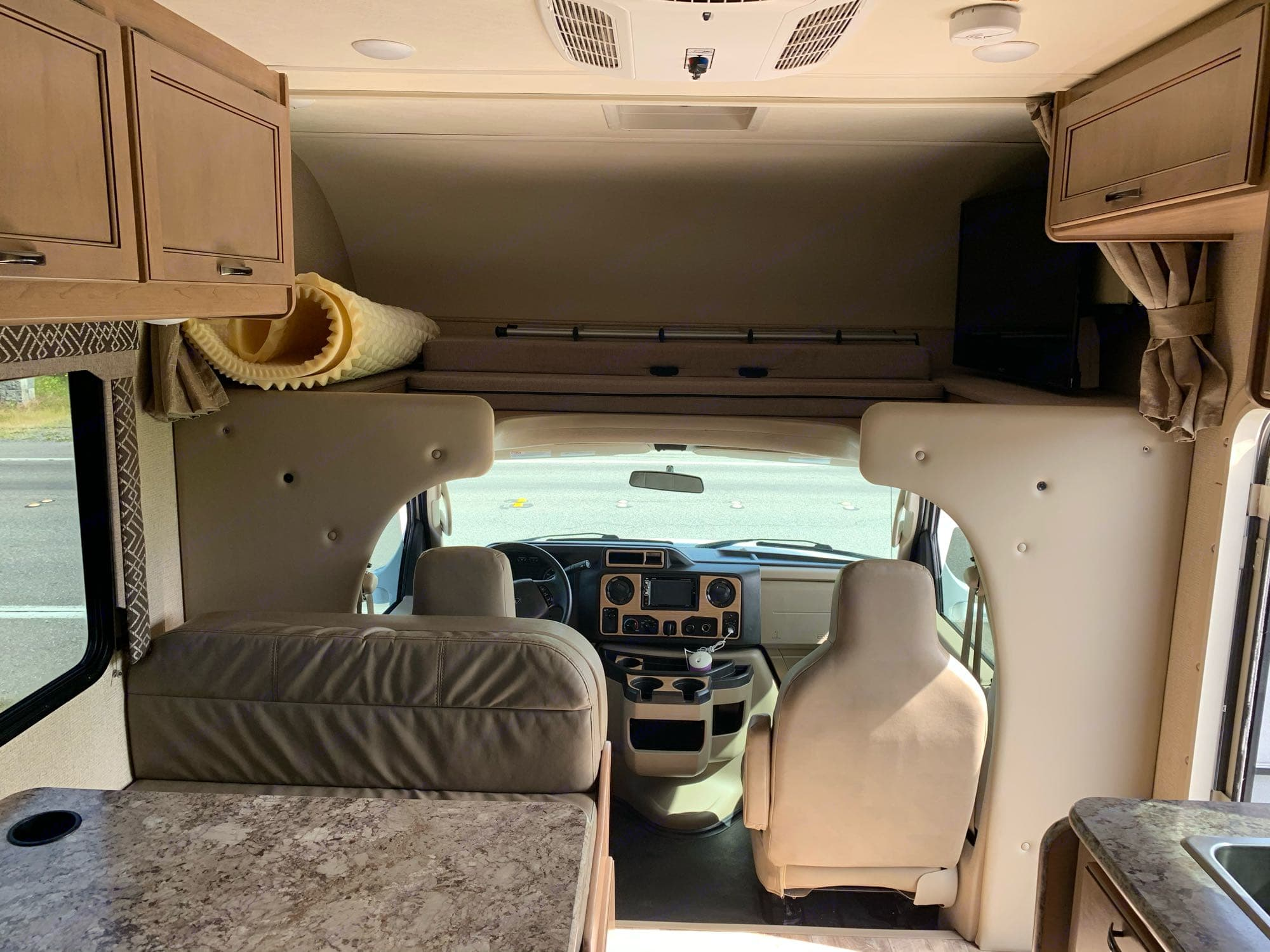 front of the cab: plenty of storage in overhead cabinets, loft bed above driver/passenger seats with tv and satellite capabilities, plus AC unit above.. Ford Fourwinds 2019