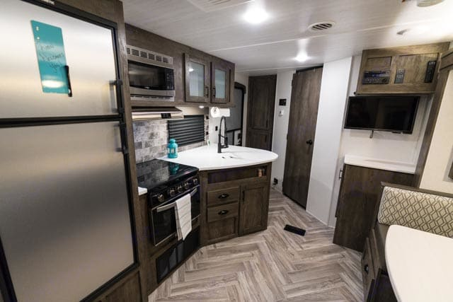 Kitchen with upgraded stainless steel appliances. ForestRiver Evo 2020