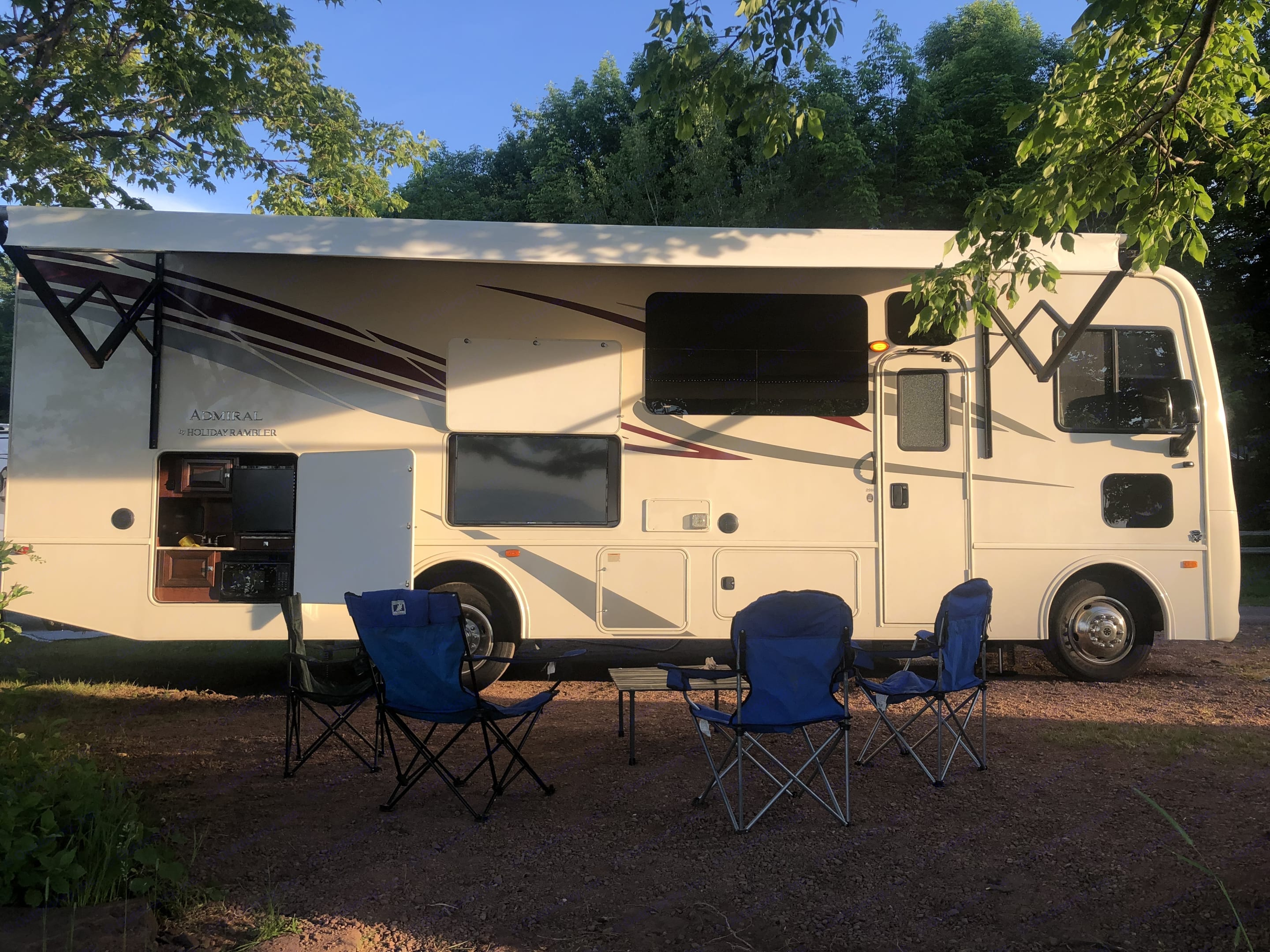 The Fun side with RV awning opened, TV, bar area, with camp chairs (also included). Ready for adventure!. HolidayRambler Admiral 2019