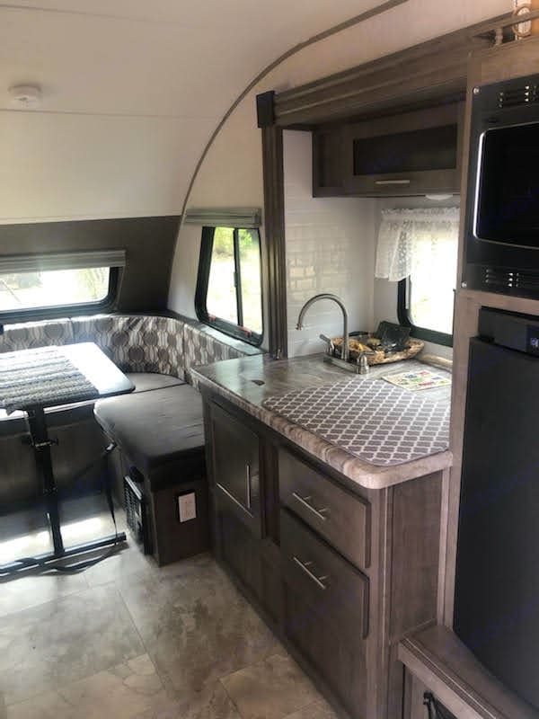 Dining table and kitchen including sink, stove, and refrigerator. Forest River R-Pod 2018