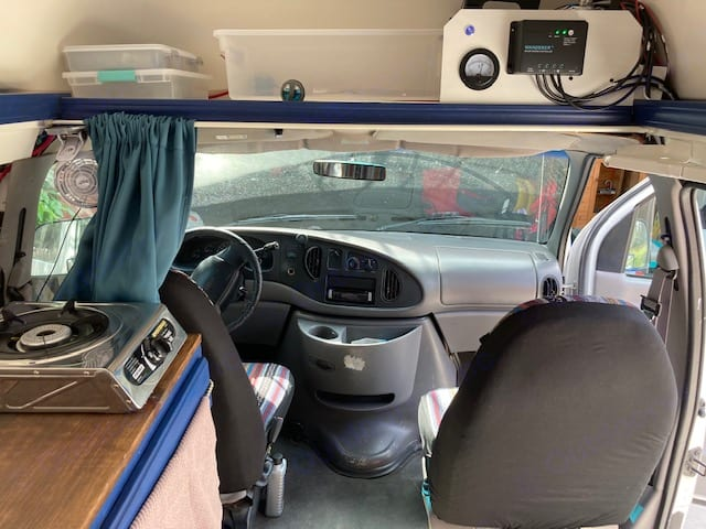 Standing in the cabin, looking at the front seats. Single propane burner. Solar panel inverter.. Ford E350 Box Van 1997